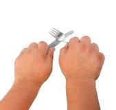 Dos manos gruesas con el cuchillo y el enchufe Foto de archivo libre de regalías
