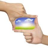 Dos manos hacen dimensión de una variable del marco con el cuadro del paisaje Imágenes de archivo libres de regalías
