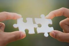 Dos manos humanas conectaron el blanco del rompecabezas, negocio común Co imagen de archivo