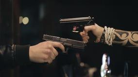 Dos manos masculinas con la toma de los armas se tienen como objetivo Cierre para arriba almacen de metraje de vídeo