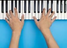 Dos manos masculinas que juegan en el teclado de la música en azul Fotografía de archivo libre de regalías