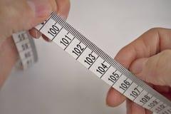 Dos manos masculinas que llevan a cabo una longitud de medición de la cinta métrica en centímetros y metros Imagen de archivo