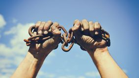Dos manos masculinas sucias envueltas en una cadena oxidada del hierro imagen de archivo