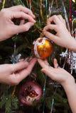 Dos manos, niño y mujeres, adornando el árbol de navidad Imágenes de archivo libres de regalías