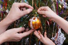 Dos manos, niño y mujeres, adornando el árbol de navidad junto Fotos de archivo