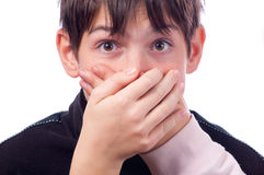 Dos manos que cubren la boca del adolescente sorprendido Imagen de archivo