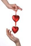 Dos manos que llevan a cabo corazones rojos Fotografía de archivo