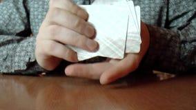 Dos manos que mezclan una cubierta de tarjetas almacen de metraje de vídeo