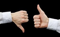 Dos manos que muestran gestos manosean con los dedos para arriba y manosean con los dedos abajo Imagen de archivo