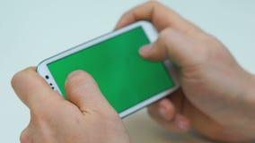 Dos manos que sostienen el teléfono elegante blanco, jugando a juegos,