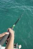 Dos manos que sostienen la caña de pescar imagen de archivo libre de regalías