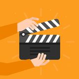 Dos manos que sostienen una chapaleta del cine en estilo plano Fotos de archivo libres de regalías