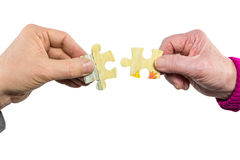 Dos manos que unen pedazos apropiados del rompecabezas Foto de archivo libre de regalías