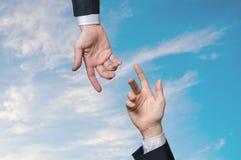 Dos manos se están alcanzando contra el cielo azul Concepto de la ayuda y de la ayuda imagen de archivo