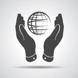 Dos manos toman el cuidado del icono del planeta del globo Imagen de archivo