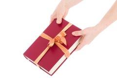 Dos manos y el libro en el embalaje del regalo aislado Imagen de archivo libre de regalías