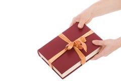 Dos manos y el libro en el embalaje del regalo aislado Fotografía de archivo