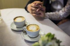 Dos manos y tazas de café Fotos de archivo