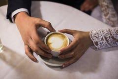 Dos manos y tazas de café Foto de archivo libre de regalías