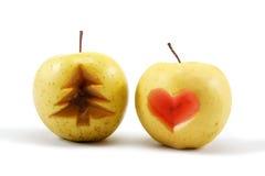 Dos manzanas con el árbol de navidad y el corazón cortados. Imagen de archivo