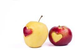 Dos manzanas con el corazón aislado en blanco Fotos de archivo libres de regalías