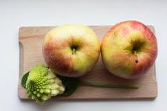 Dos manzanas con la hoja del bróculi y de la espinaca Fotografía de archivo