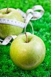 Dos manzanas en hierba y una con una cinta métrica Foto de archivo