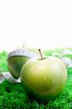 Dos manzanas en hierba y una con una cinta métrica Fotografía de archivo libre de regalías