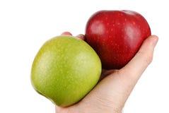 Dos manzanas en una mano Foto de archivo libre de regalías