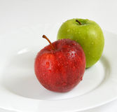 Dos manzanas en una placa blanca Foto de archivo libre de regalías