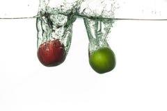 Dos manzanas frescas que caen en el agua foto de archivo