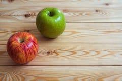 Dos manzanas frescas Manzanas rojas y verdes en el fondo de madera Imágenes de archivo libres de regalías
