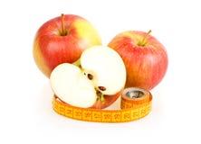 Dos manzanas rebanadas rojas y cinta de medición Foto de archivo libre de regalías