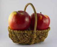 Dos manzanas rojas en cesta Foto de archivo