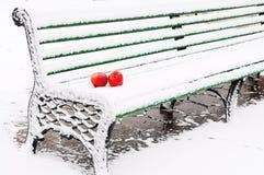 Dos manzanas rojas en un banco viejo en la nieve foto de archivo