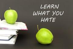 Dos manzanas verdes y los libros abiertos con el texto aprenden lo que usted odia Fotografía de archivo libre de regalías