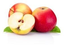 Dos manzanas y mitades rojas con las hojas del verde aisladas Foto de archivo