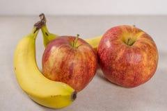 Dos manzanas y plátanos aislados en un fondo de Gray White Grey Marble Slate fotografía de archivo libre de regalías
