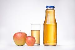 Dos manzanas y una botella de zumo de manzana en el fondo blanco Imágenes de archivo libres de regalías
