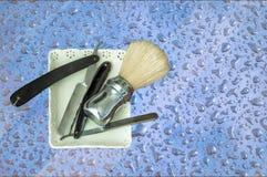 Dos maquinillas de afeitar viejas y brocha de afeitar en un fondo coloreado Foto de archivo