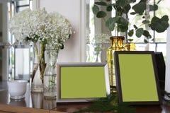 Dos marcos de la foto rodean con la flor blanca y la licencia verde fotografía de archivo libre de regalías
