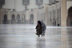 Dos marroquíes funcionados con a través de la lluvia Imagen de archivo
