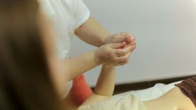 Dos masajistas dan masajes a las manos de una muchacha en un salón del balneario Masaje de Ayurvedic en cuatro manos metrajes