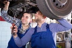 Dos mecánicos de coche en el taller Fotografía de archivo libre de regalías