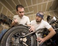 Dos mecánicos de la motocicleta que colocan una defensa Imágenes de archivo libres de regalías