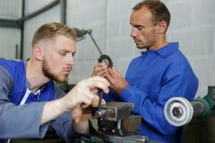 Dos mecánicos de sexo masculino que examinan piezas imagen de archivo