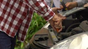 Dos mecánicos de sexo masculino que fijan el fallo mecánico de coche, servicio de mantenimiento del vehículo metrajes