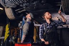 Dos mecánicos que equilibran el ` s del coche ruedan adentro un taller Imagenes de archivo