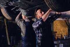 Dos mecánicos que equilibran el ` s del coche ruedan adentro un taller Imagen de archivo libre de regalías