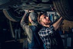Dos mecánicos que equilibran el ` s del coche ruedan adentro un taller Imágenes de archivo libres de regalías